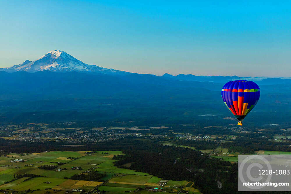 Aerial view of hot air balloon floating over farmland and Mt. Rainer in the distance.