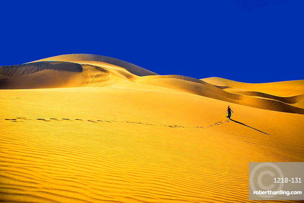 Woman walking away on sand dune, Huacachina Oasis, Peru, South America