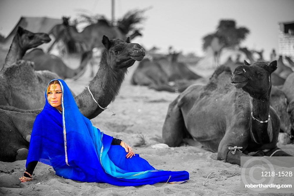 Girl with camels at the Pushkar Camel Fair, Pushkar, Rajasthan, India, Asia