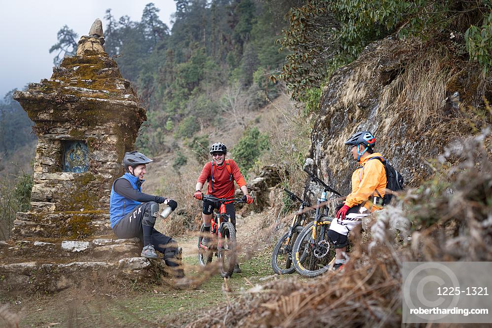 Mountain bikers take a break near a moss covered Tibetan chorten in the Himalayas in the Gosainkund region, Nepal, Asia