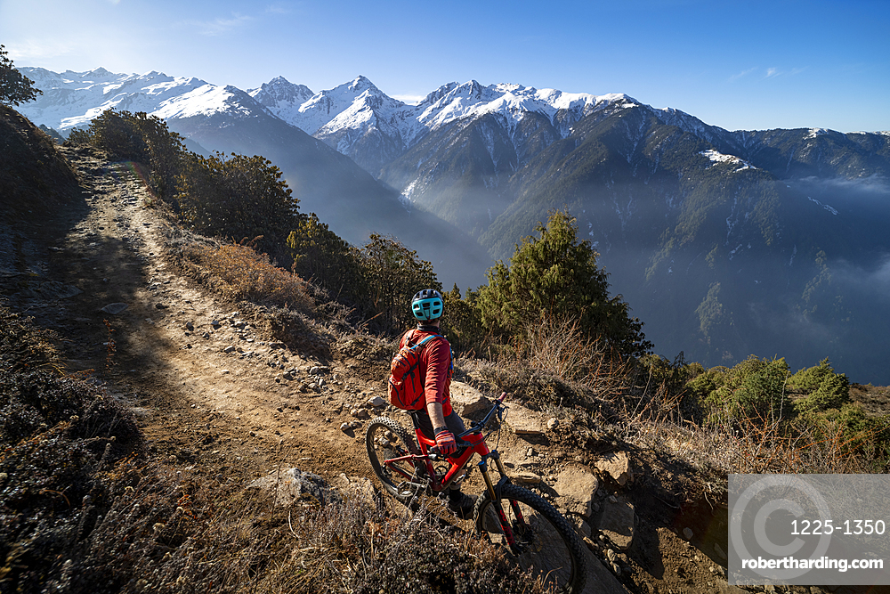 A mountain biker takes a rest on an Enduro style single track trail in the Nepal Himalayas near the Langtang region, Nepal, Asia