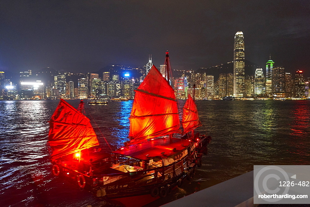 Traditional Chinese junk boat for tourists on Victoria Harbour illuminated at night, Hong Kong