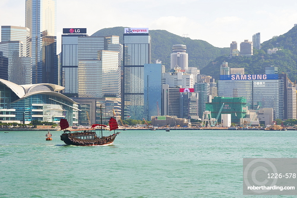 Traditional junk boat on Victoria Harbour with city skyline behind, Hong Kong