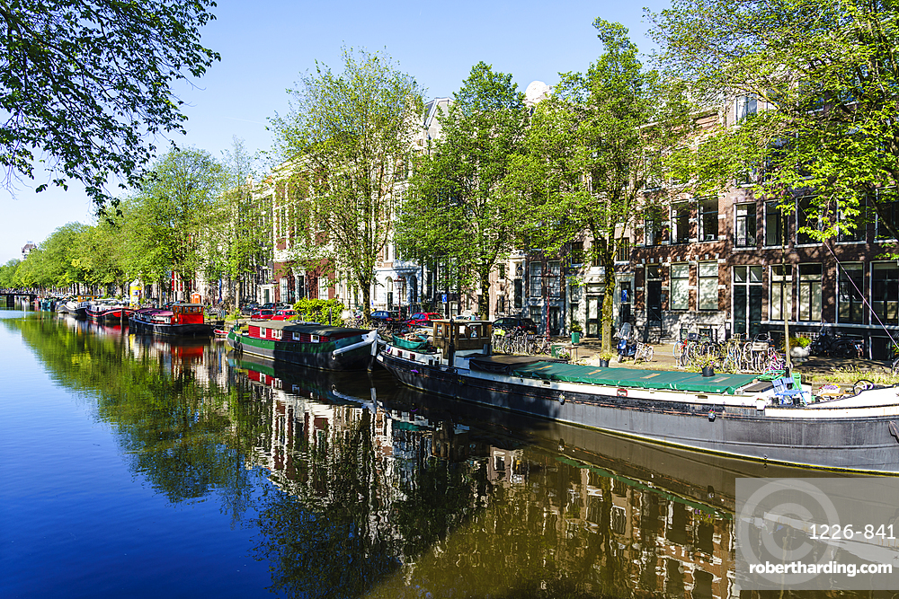 Old gabled buildings reflecting in a canal, Amsterdam, Netherlands