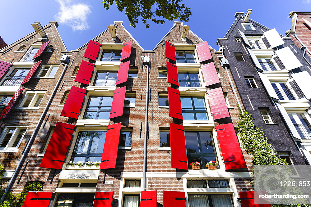 Red shutters on traditional dutch style building, Amsterdam, Netherlands