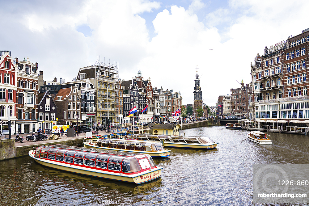 Tourist boats on Amstel River near Muntplein and Rokin, Amsterdam, Netherlands