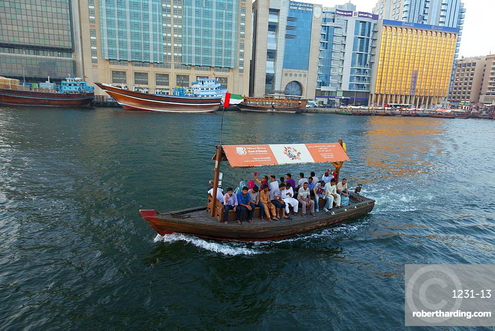 A water taxi carries passengers across Dubai Creek, Dubai, United Arab Emirates, Middle East
