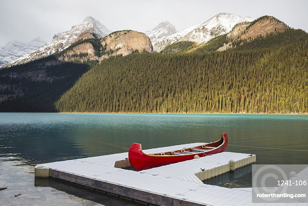 Red canoe and dock in Lake Louise with snow-covered mountains, Banff National Park, UNESCO World Heritage Site, Alberta, The Rockies, Canada, North America