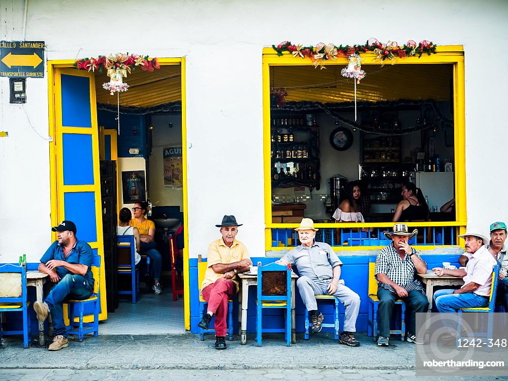 Men sit outside a bar, Jardin, Antioquia, Colombia, South America