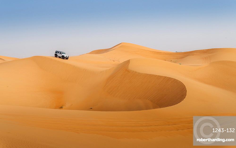 Offroad vehicle on sand dunes near Dubai, United Arab Emirates, Middle East