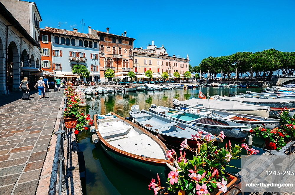 Boats on marina with tourists at cafes and restaurants at Desenzano del Garda, Lake Garda, Lombardy, Italian Lakes, Italy, Europe