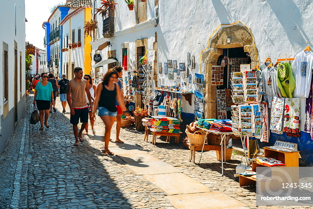Tourists and shops in the typical alleys of the ancient fortified village of Obidos, Oeste Leiria District, Portugal, Europe