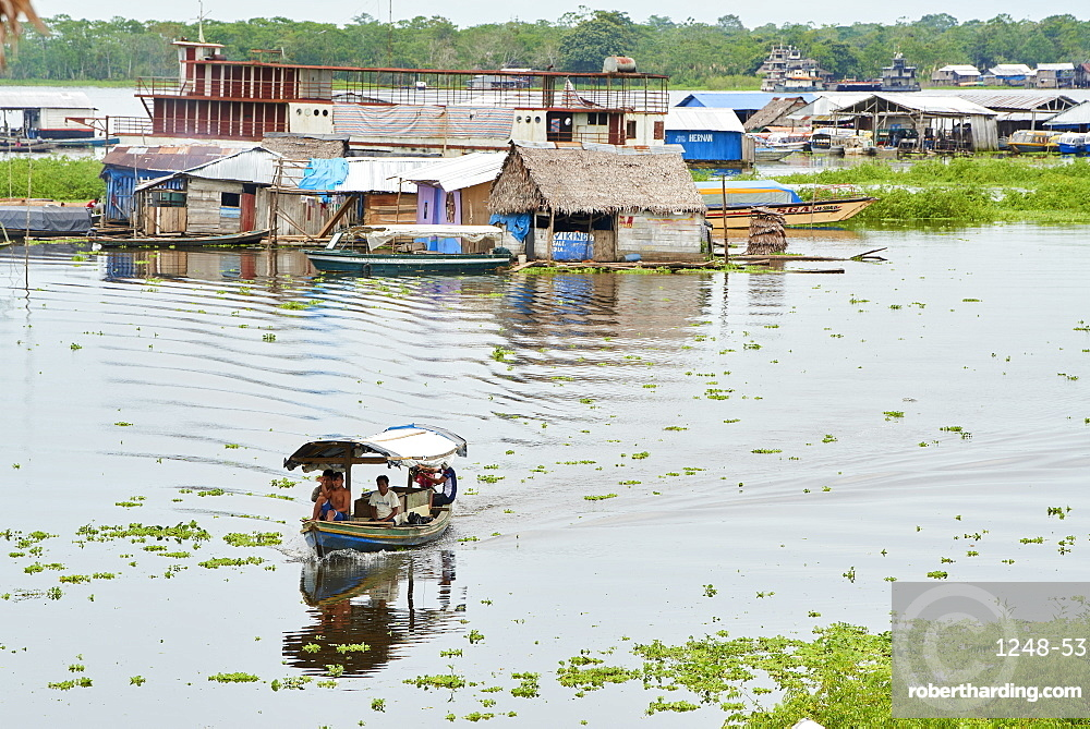 Riverboat in Nanay River with floating houses in the background, Iquitos, Peru, South America