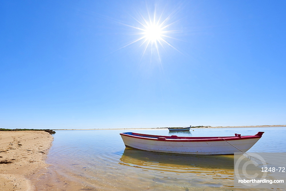 The sun shines above a small fishing boat on transparent lagoon water in Cacela Velha, Algarve, Portugal, Europe