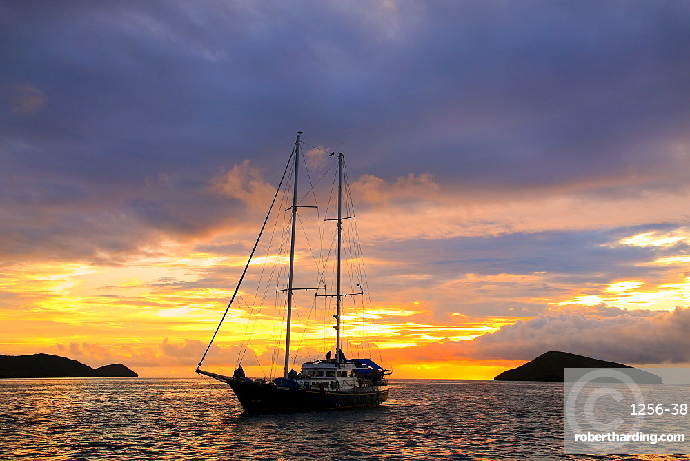 Silhouetted tourist sailboat at sunrise anchored near Chinese Hat island in Galapagos National Park, Ecuador