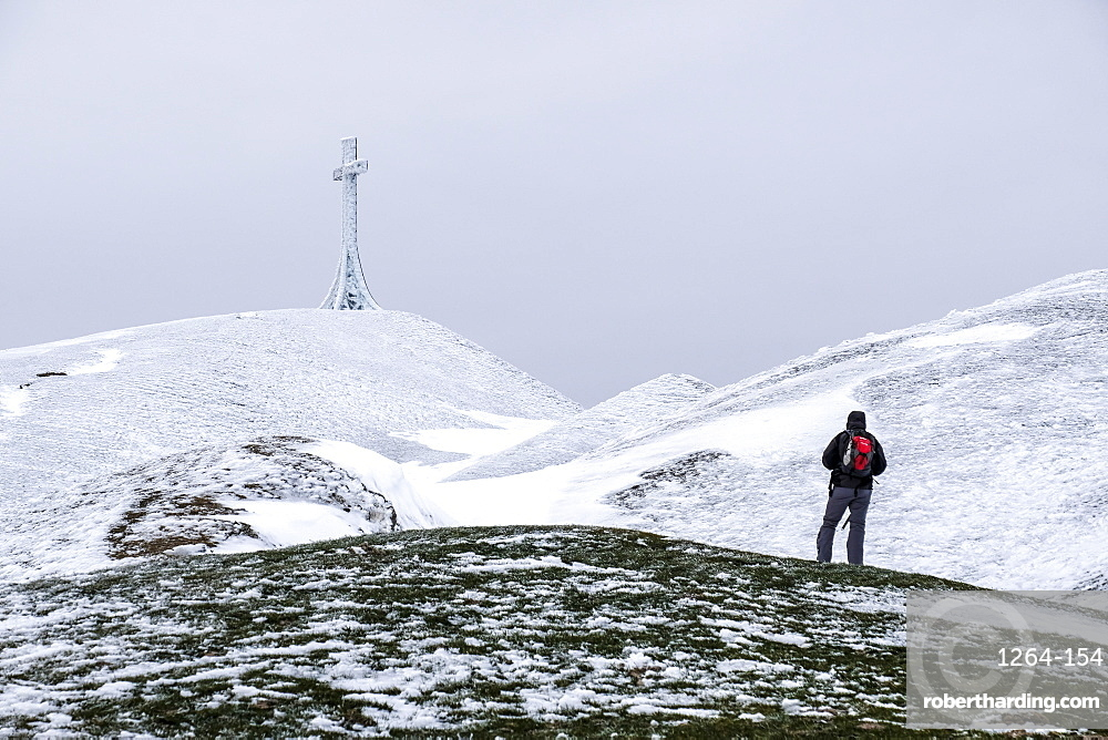Hiker reaching the summit cross of Monte Catria in winter, Apennines, Umbria, Italy, Europe