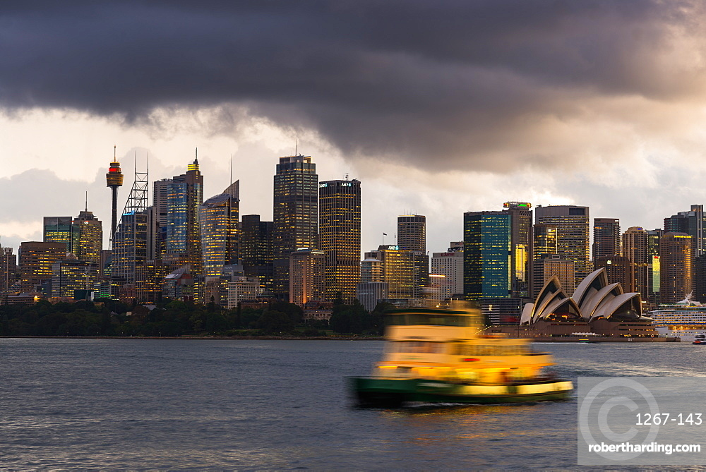A ferry in Sydney Harbour at dusk with the Opera House and city skyline, Sydney, New South Wales, Australia, Pacific