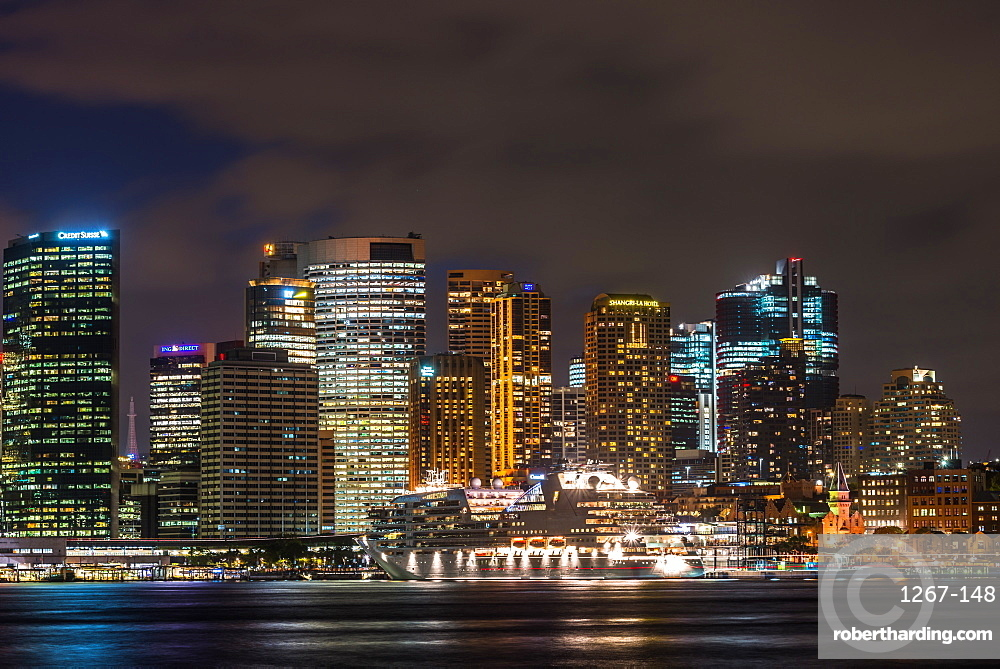 Large cruise ship docked at International Terminal in Sydney harbour after dark with city skyline, New South Wales, Australia.