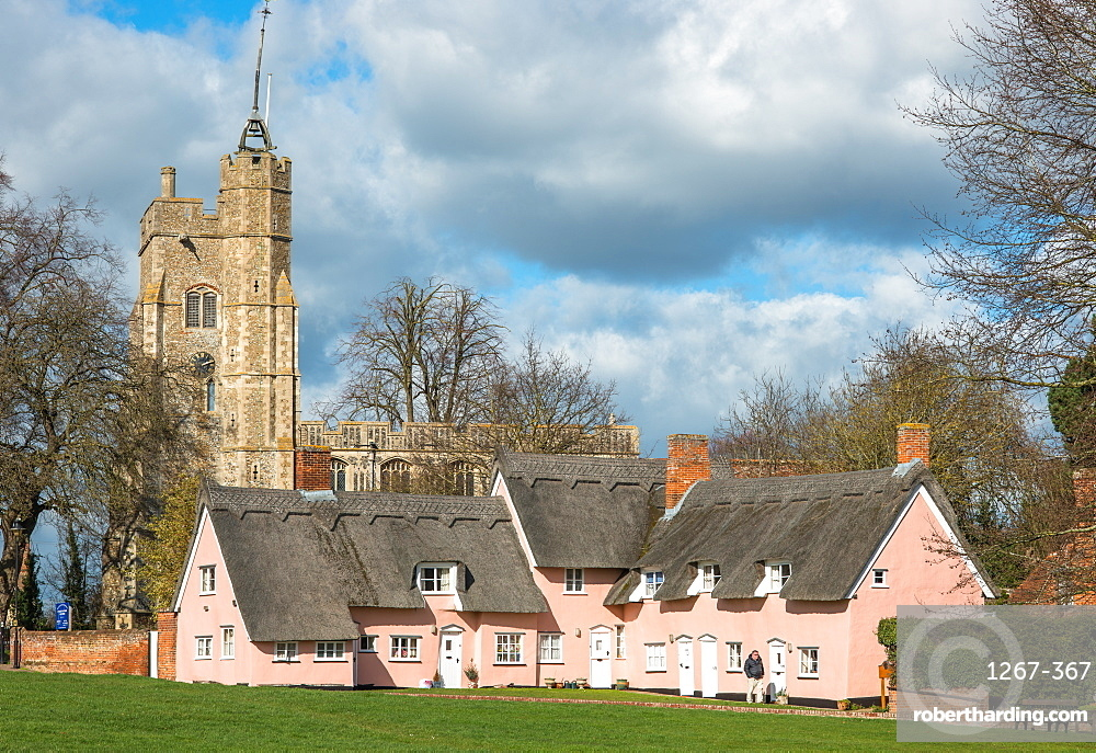 The village green in Cavendish with the medieval St Mary church tower & traditional pink thatched cottages, Suffolk, England, UK