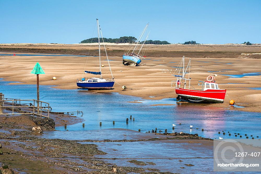 Colourful boats on sandbanks low tide, East Fleet river estuary, Wells next the sea, North Norfolk coast, East Anglia England UK
