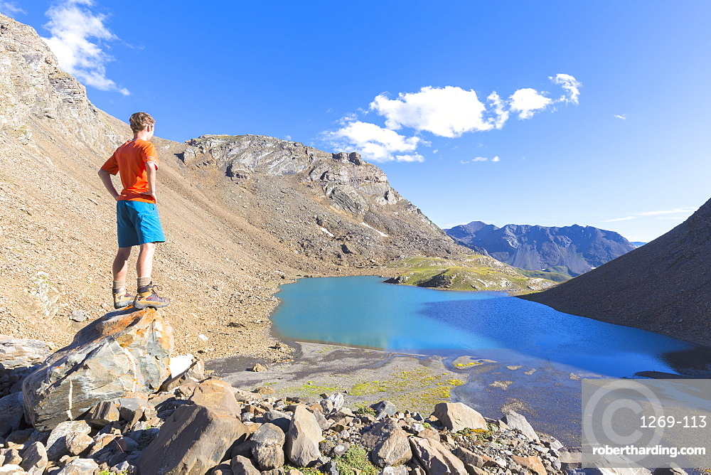 A boy looks at Lai da Fasch'Alba from above, Val Tasna, Engadine Valley, Graubunden, Switzerland, Europe