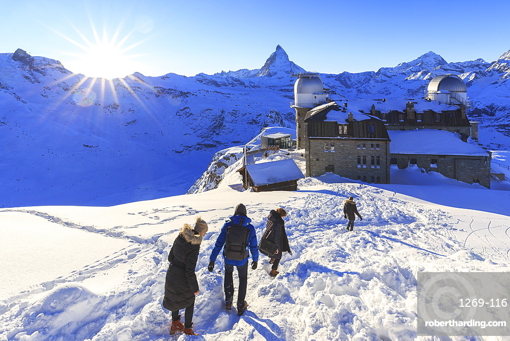 Tourists walk in the snow near the astronomical observatory of Gornergrat, Zermatt, Canton of Valais (Wallis), Switzerland, Europe