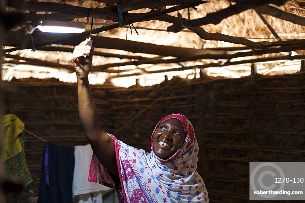 A woman smiling as she turns on the new solar light in her mud hut, Tanzania, East Africa, Africa
