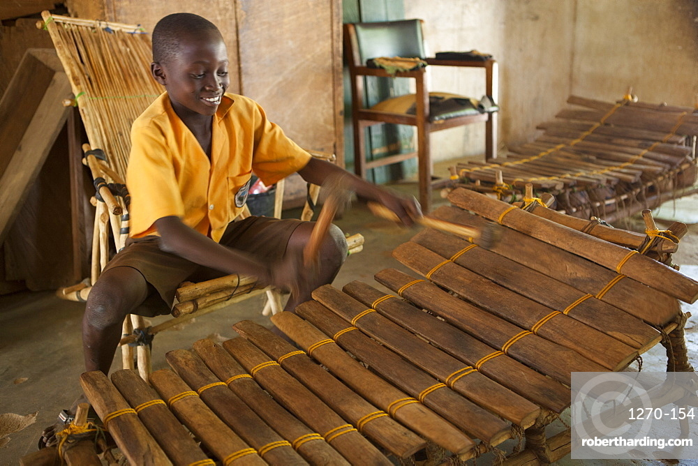 A school boy playing music on a large wooden xylophone at his primary school in Ghana, Africa