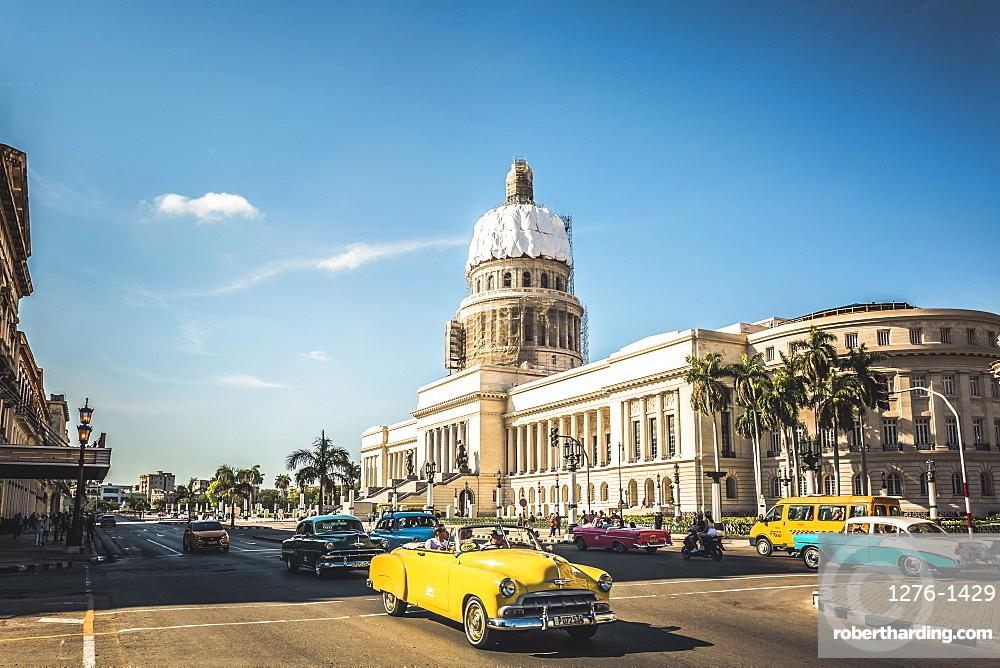 A yellow American classic car outside El Capitolio in Havana, La Habana, Cuba, West Indies, Caribbean, Central America