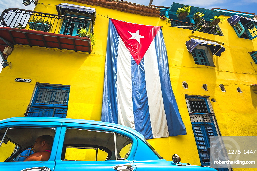 Old American classic car and huge Cuban flag on yellow building in Havana, La Habana, Cuba, West Indies, Caribbean, Central