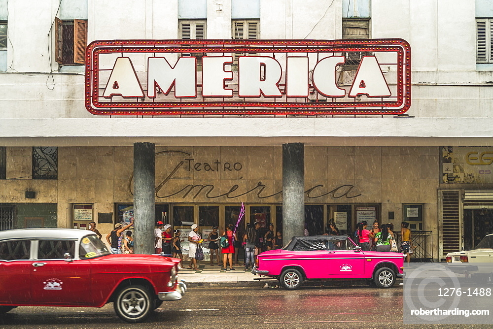 Pink and red vintage cars outside Teatro America in rain, La Habana, Havana, Cuba, West Indies, Caribbean, Central America