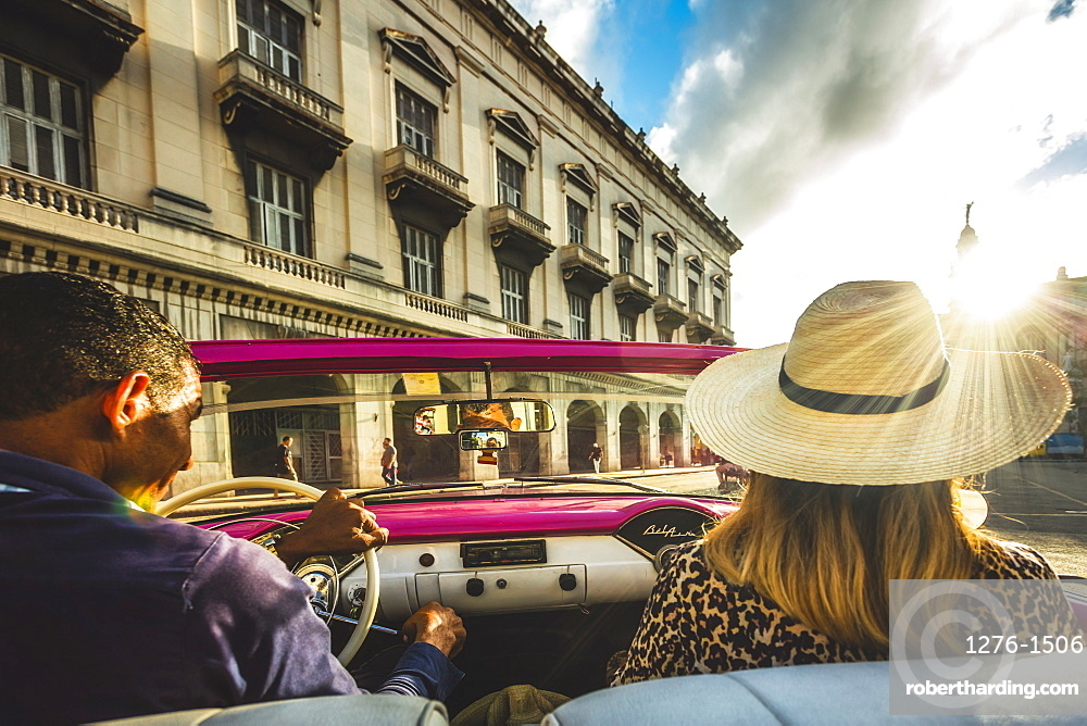 Tourist enjoying classic car ride at sunset in La Habana, Havana, Cuba, West Indies, Caribbean, Central America