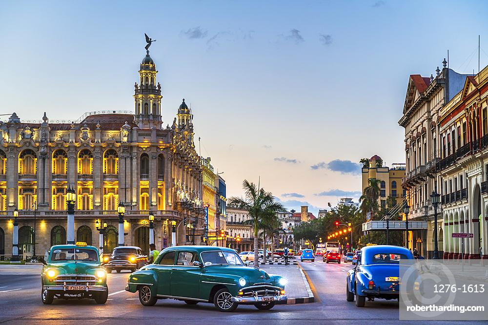 Vintage American cars turning and The Gran Teatro de La Habana at dusk, UNESCO, Havana, Cuba, West Indies, Caribbean, Central America