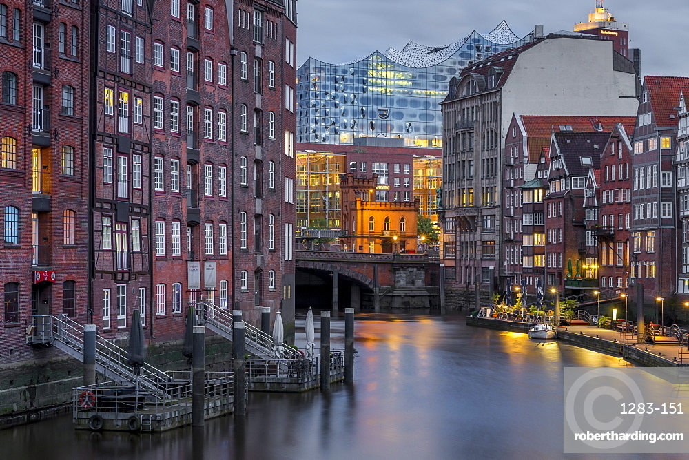 Historical buildings at Nikolaifleet with view to the Elbphilharmonie building in the background at dusk, Hamburg, Germany, Europe