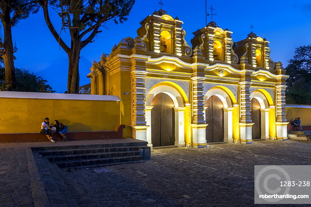 Illuminated entrance gate of the chapel El Calvario near Antigua at dusk, Guatemala, Central America