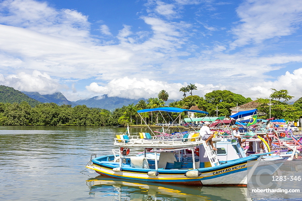 Colorful tour boats anchoring at the port of Paraty with view to the Serra da Bocaina mountain range, Rio de Janeiro, Brazil, South America