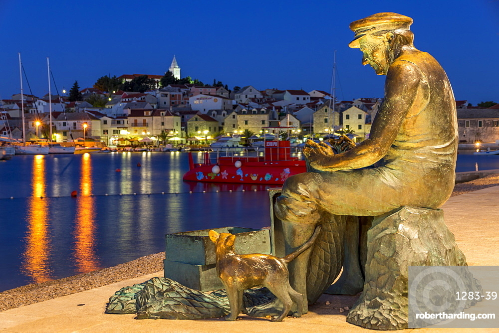 Fisherman statue with view to the old town of Primosten in the background