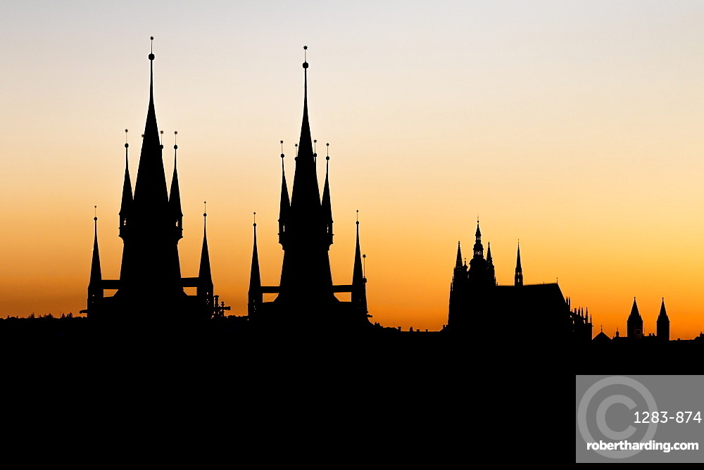 Silhouettes of Our Lady before Tyn Church and St. Vitus Cathedral at sunset, Prague, Bohemia, Czech Republic, Europe