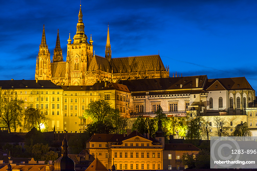 Illuminated Prague Castle and St. Vitus Cathedral seen from the banks of Vltava River, Prague, Bohemia, Czech Republic, Europe