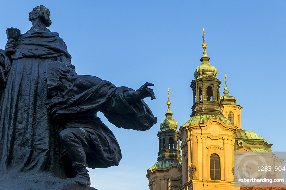 Jan Hus Monument and St. Nicholas' Church seen from the old town market square in the morning, Prague, Bohemia, Czech Republic