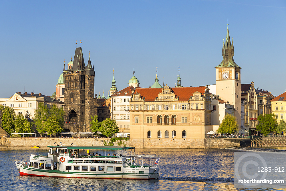 Tourist boat on Vltava River passing the Old Town Bridge Tower and the Old Town Water Tower, Prague, Bohemia, Czech Republic