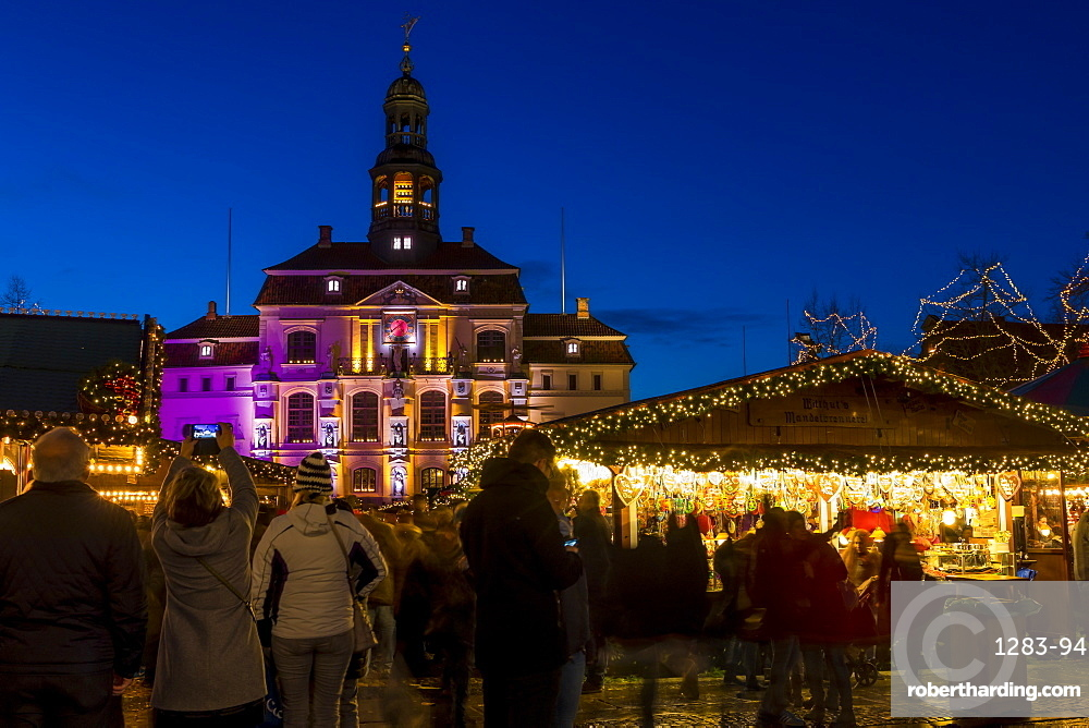 Christmas market at the main square of Lueneburg with view to the town hall at dusk