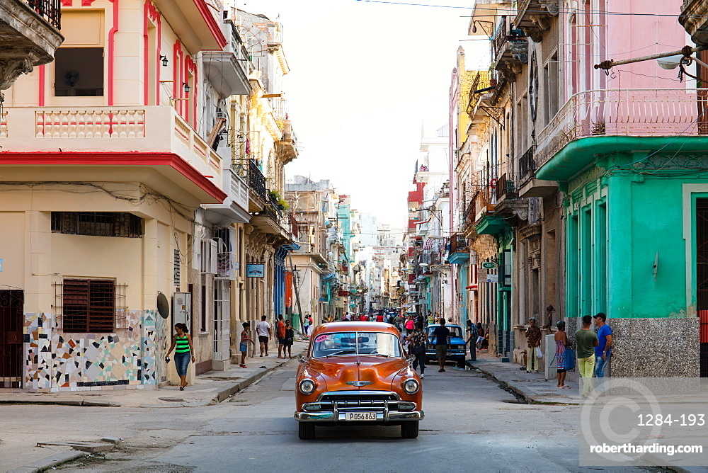 Red vintage car drives along old colourful street in Havana, Cuba, West Indies, Caribbean, Central America