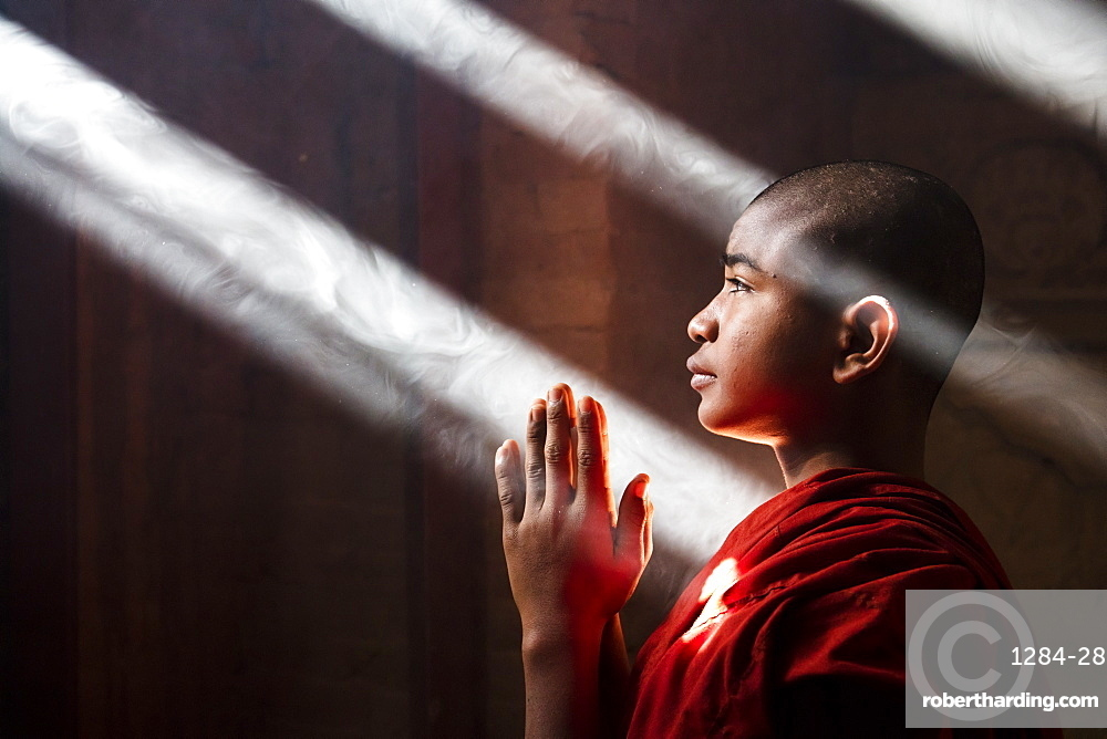 Young monk praying and covered with light beams in a temple in Bagan, Myanmar (Burma)