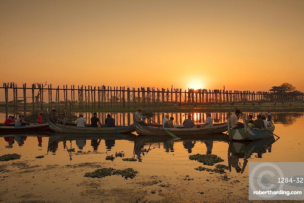 Sunset at U Bein bridge, oldest and longest teak bridge in the world, across Lake Taungthaman, Amarapura, Myanmar (Burma), Asia