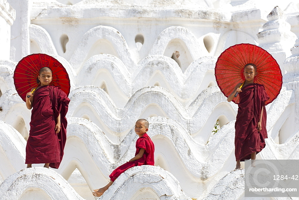 Three young monks dressed in red, with red parasols at the Myatheindan Pagoda (White Temple) in Mingun, Myanmar (Burma)