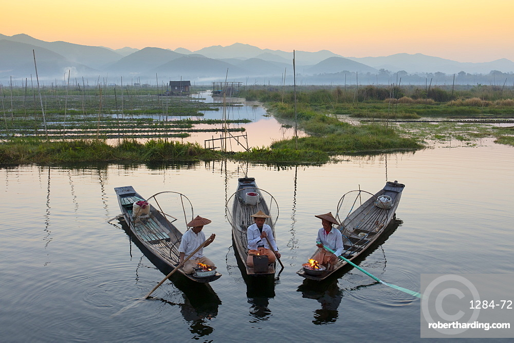 Three fishermen keep warm in their long tail fishing boats at dawn near the floating gardens on Inle Lake, Shan State, Myanmar (Burma), Asia