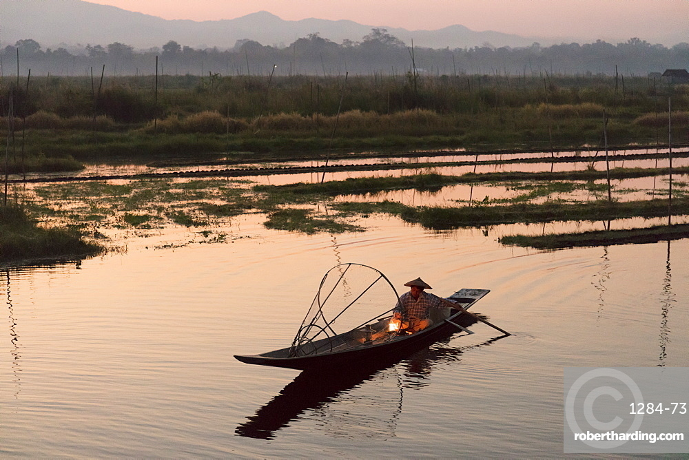 A fisherman keeps warm in his long tail fishing boat at dawn near the floating gardens on Inle Lake, Shan State, Myanmar (Burma), Asia