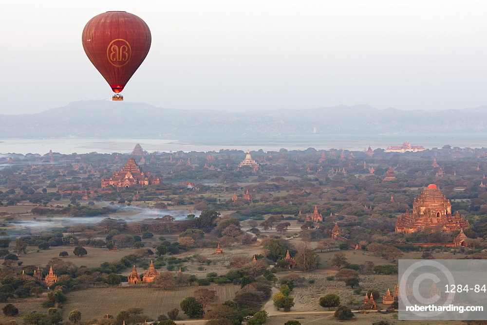 Hot air balloon flies over ancient Buddhist temples at dawn, Bagan (Pagan), Mandalay Region, Myanmar (Burma), Asia