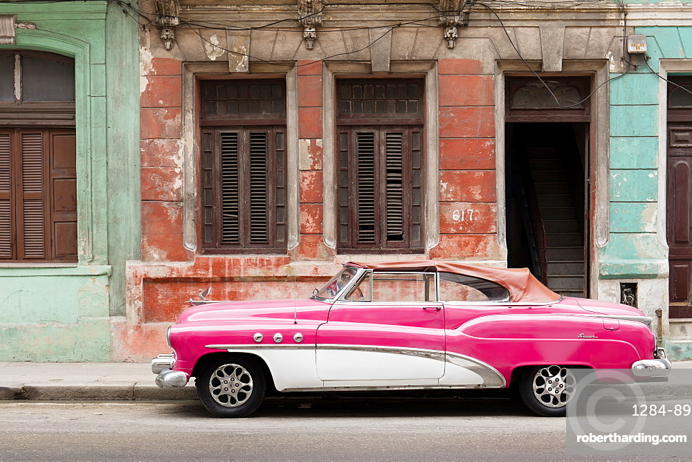A pink and white vintage American convertible car parked on a street in Havana, Cuba, West Indies, Caribbean, Central America